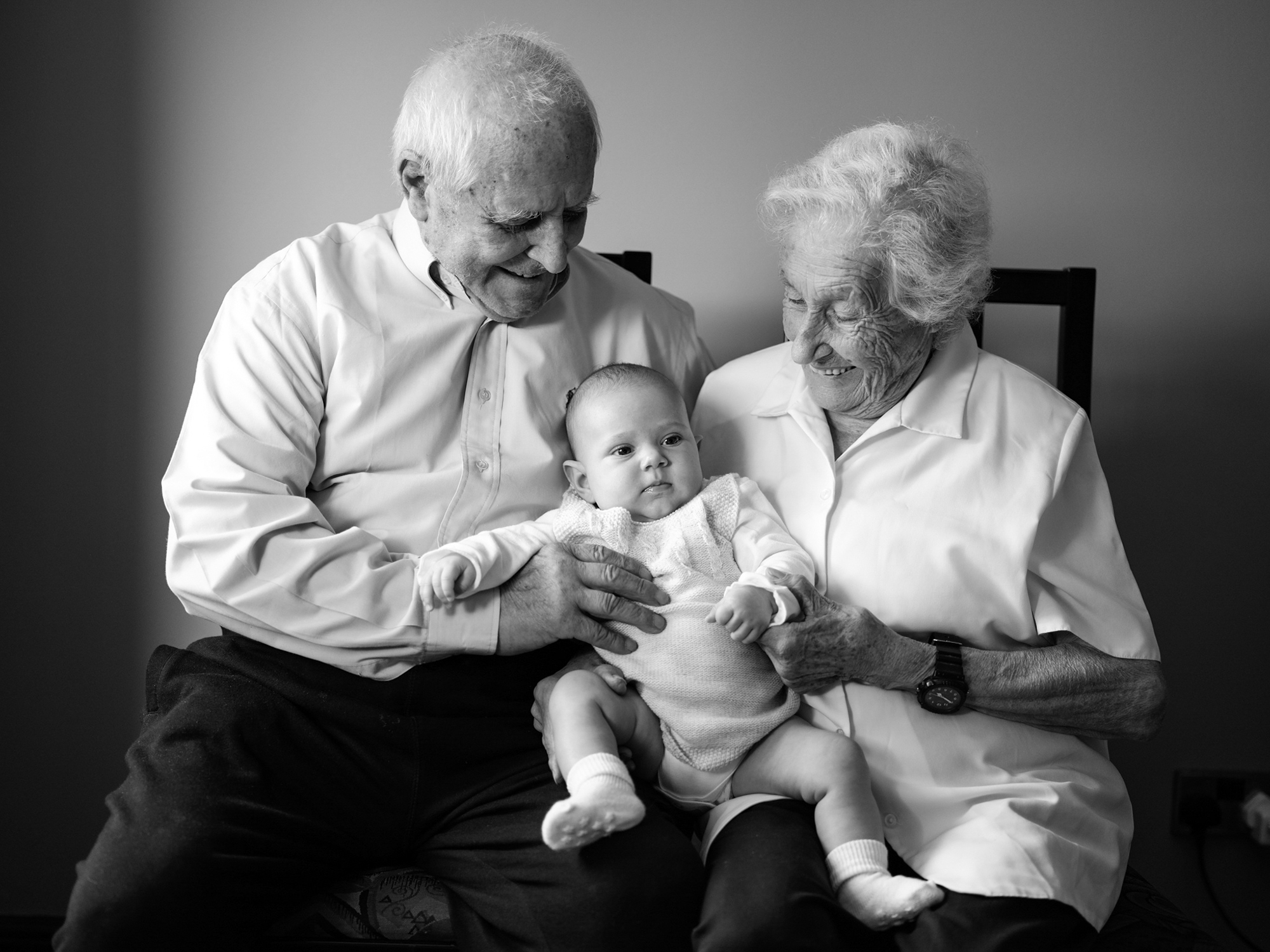 Grandparents hold their grandchild for a photograph
