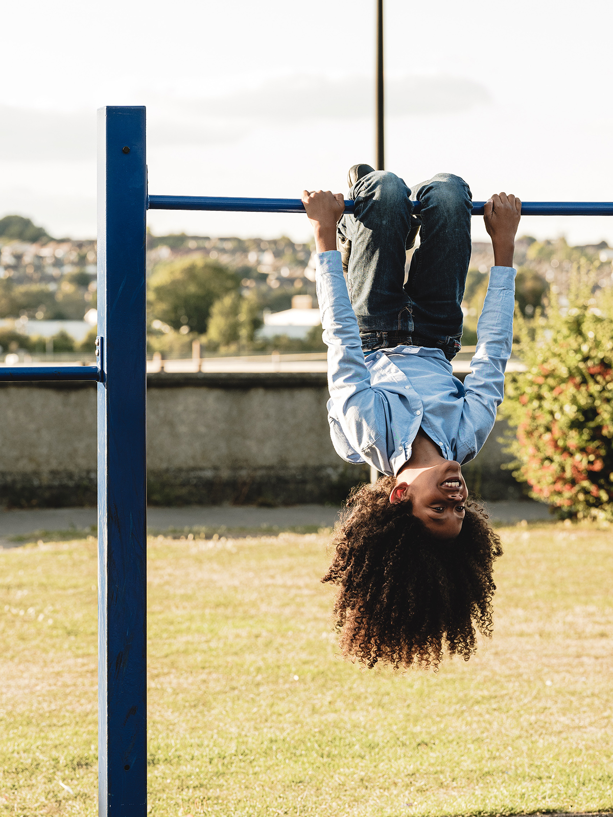 A child swings from monkey bars during a photoshoot