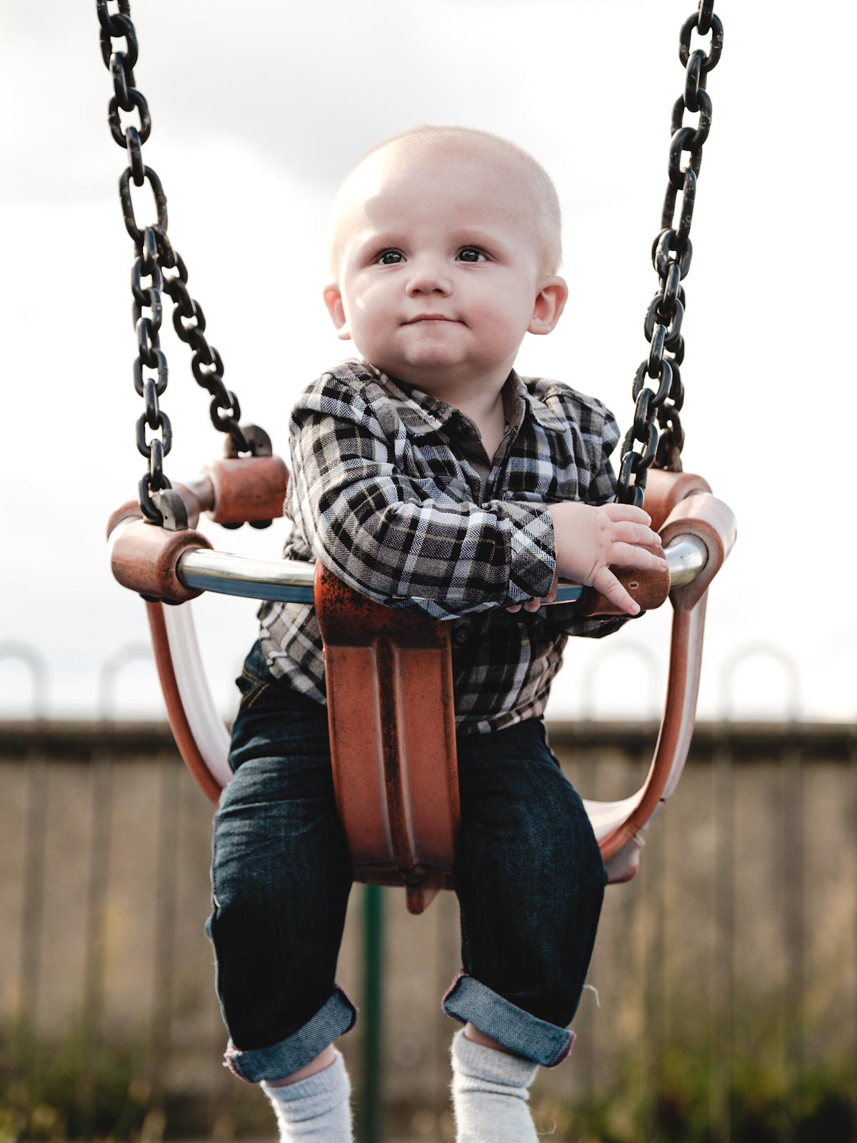 A young child wearing a shirt and jeans is sitting in a swing