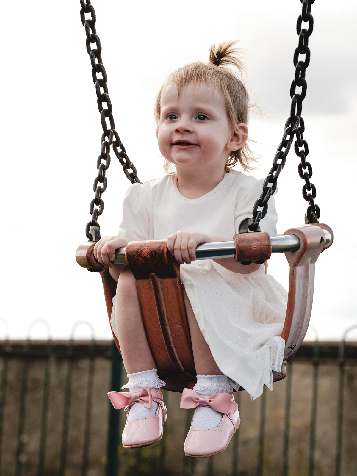 A young girl wearing a white dress and pink shoes with bows on is sitting in a swing
