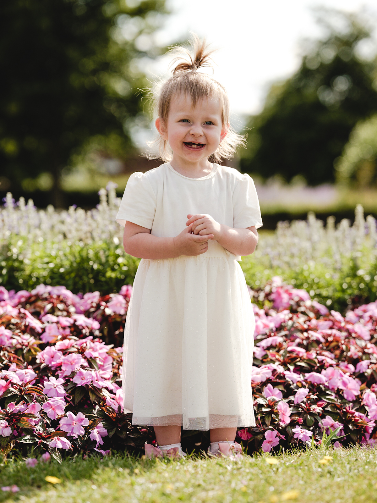 Little girl smiles and poses for a photo during a family photoshoot