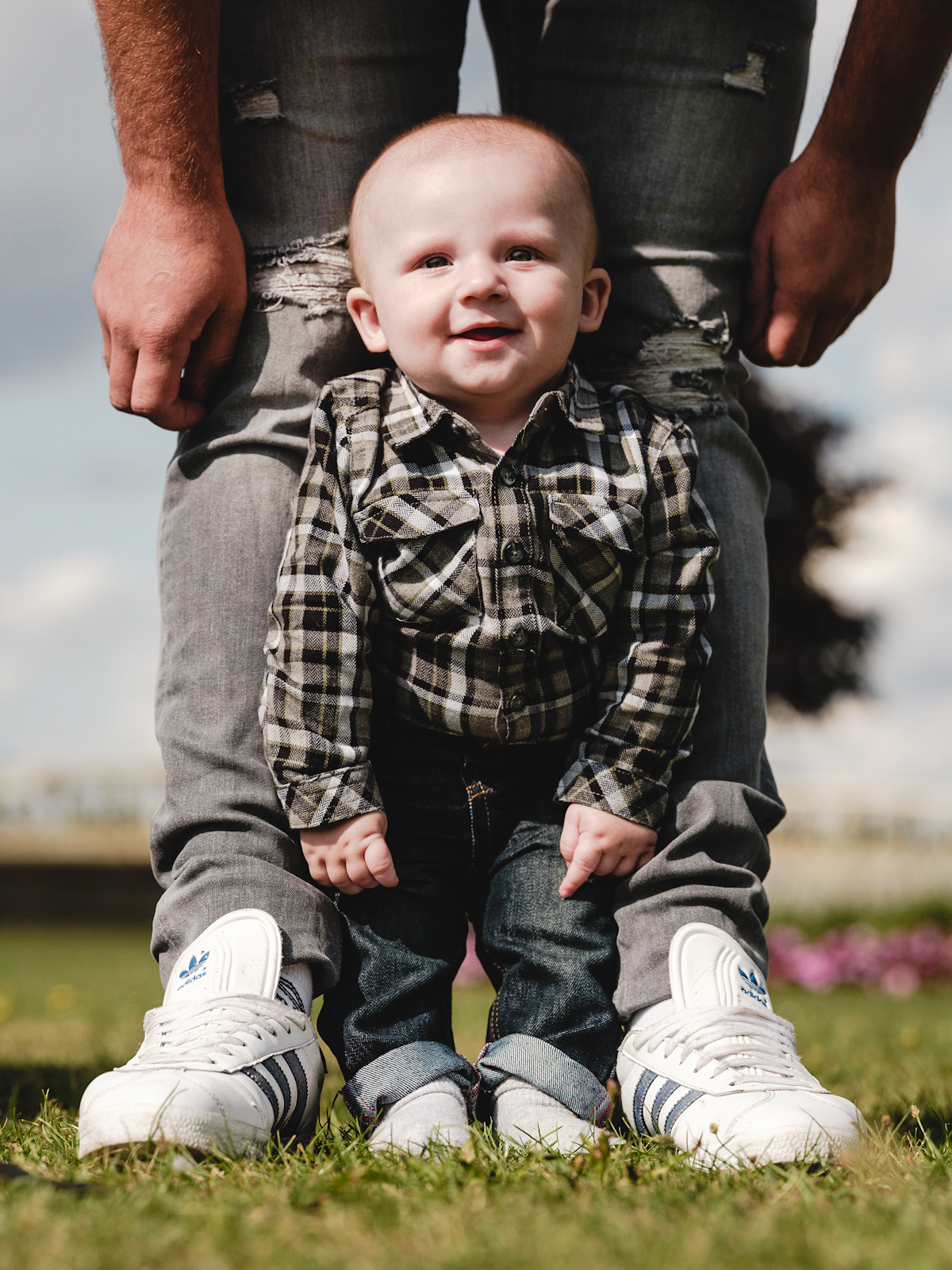 Young child is leaning against his father's legs for a photo