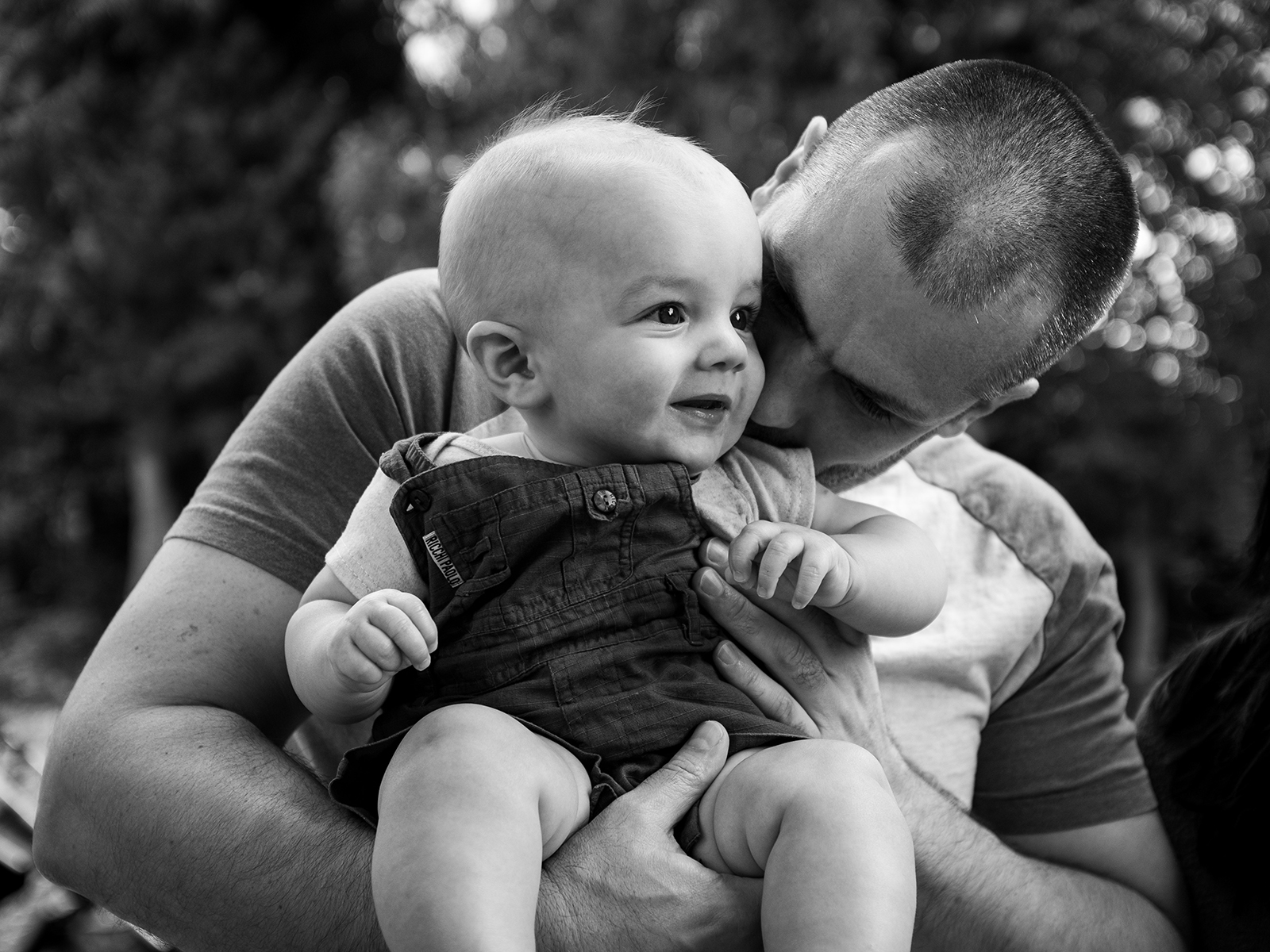A baby boy is held by his father during a photoshoot