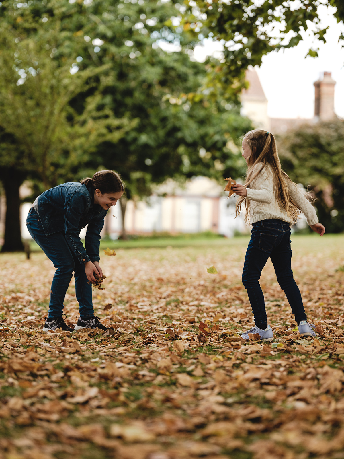 two sisters play in fallen leaves during a family photoshoot