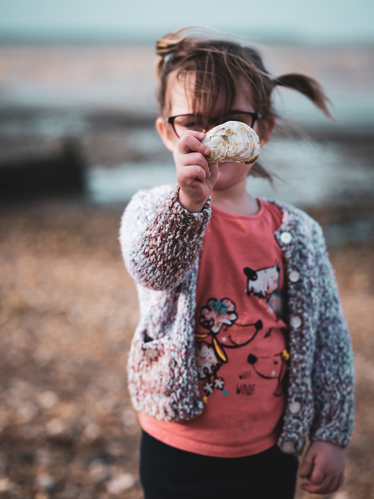 A young girl holds up a seashell she found on the beach