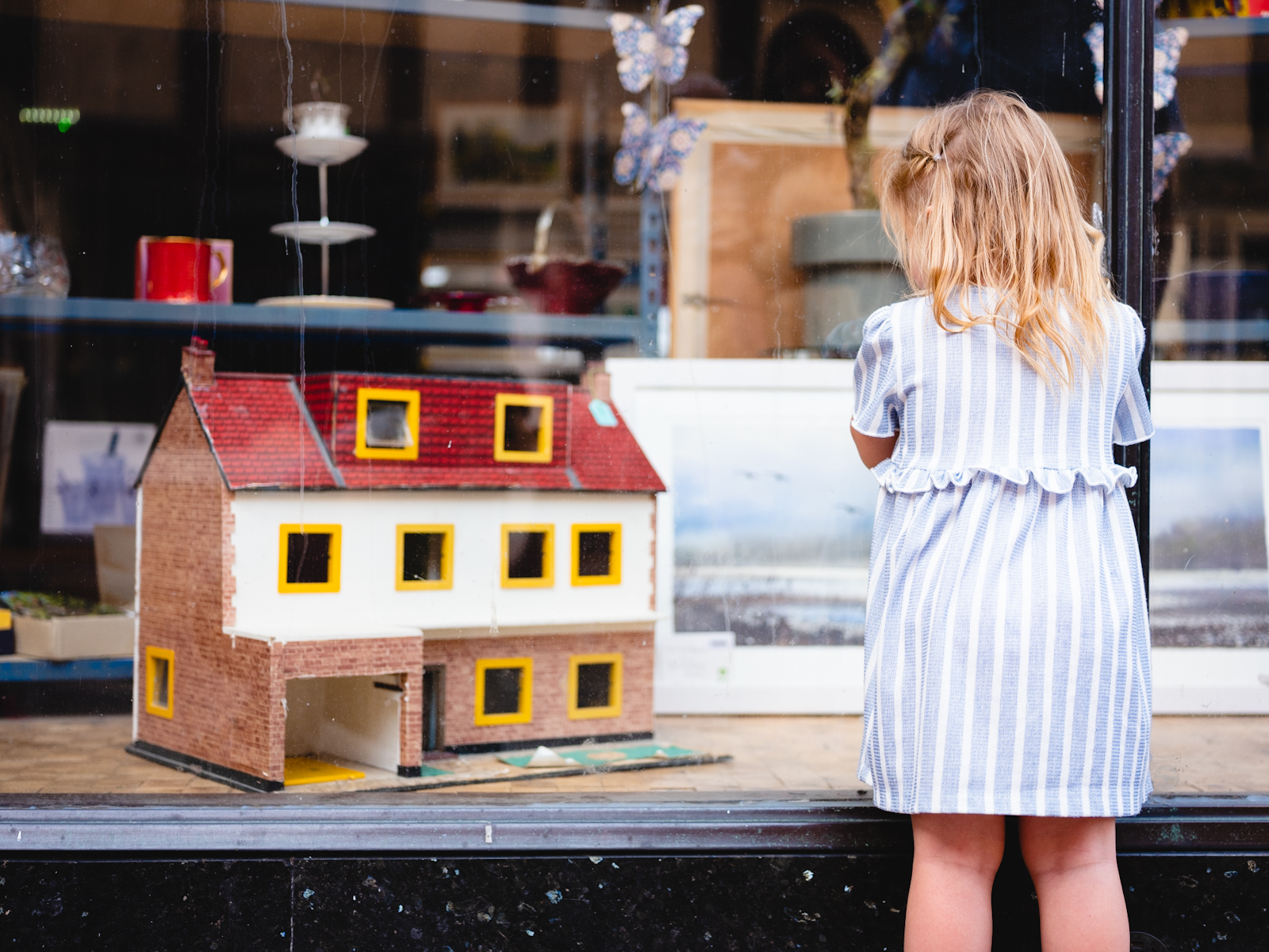 Young girl looks through a shop window at a Dolls House