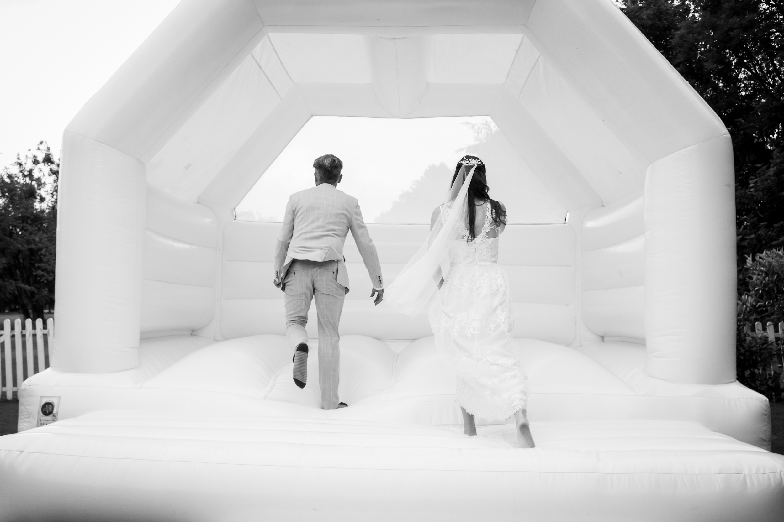 Bride and Groom on White Bouncy Castle on their wedding day